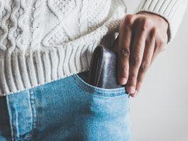 moški, ki pospravlja denarnico v žep