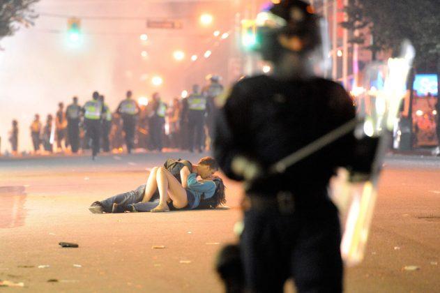 Slika para, ki se poljublja med protesti v Kanadi po finalu hokejske lige.