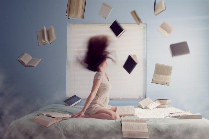 Ženska, ki kleči na postelji in se uči. zaradi stresa meče knjige po zraku.