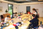 Učenci in odrasli sedijo za veliko mizo